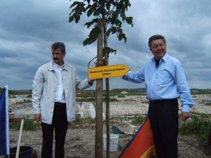 So fern und doch so nah: am Partnerschaftsbaum wird ein Wegweiser mit Entfernungsangabe angebracht